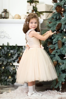 Schattig klein meisje in een weelderige beige jurk hangt kegels aan de kerstboom die in het huis staat