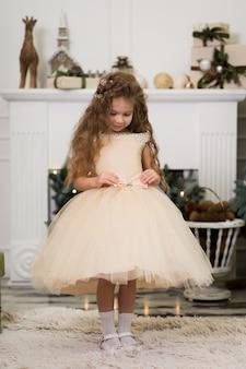Schattig klein meisje in een weelderige beige jurk poseren in de buurt van de kerstboom