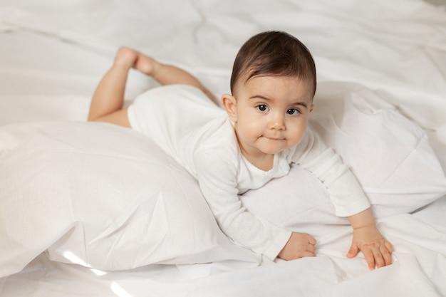 Schattig klein meisje in een witte romper ligt in bed met katoenen linnen. hoge kwaliteit foto.