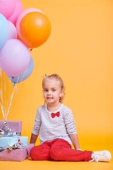 Schattig klein meisje in gestreepte trui en rode broek op zoek naar jou zittend op de vloer met een heleboel ballonnen en geschenkdozen in de buurt