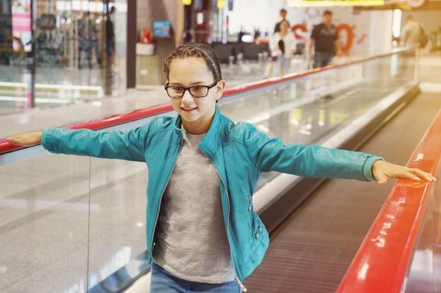 Schattig klein meisje in glazen en blauwe jas staande op de bewegende roltrap op de luchthaven.