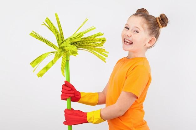 Schattig klein meisje in handschoenen met een bezem