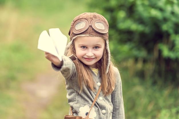Schattig klein meisje in helm piloot met papieren vliegtuigje