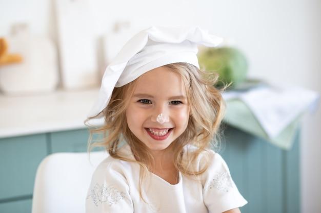 Schattig klein meisje in het kostuum van de kokchef-kok