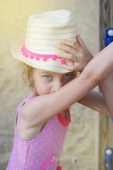 Schattig klein meisje in hoed, op speelplaats. zomervakantie.