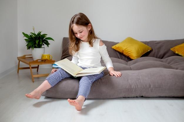 Schattig klein meisje in jeans en een witte coltrui leest en doet huiswerk zittend op het bed