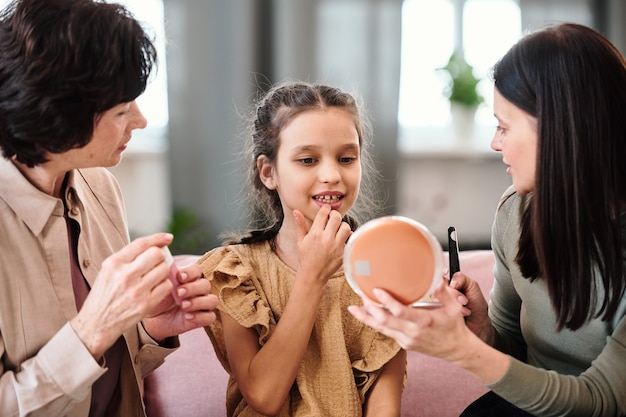 Schattig klein meisje in jurk die voedzame balsem op de lippen aanbrengt terwijl ze in de spiegel kijkt, vastgehouden door een jonge brunette vrouw die haar schoonheidsadvies geeft