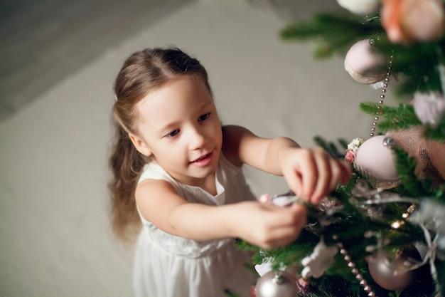 Schattig klein meisje in jurk kerstboom versieren. nieuwjaar.