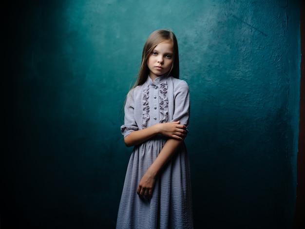 Schattig klein meisje in jurk poseren droevige blik
