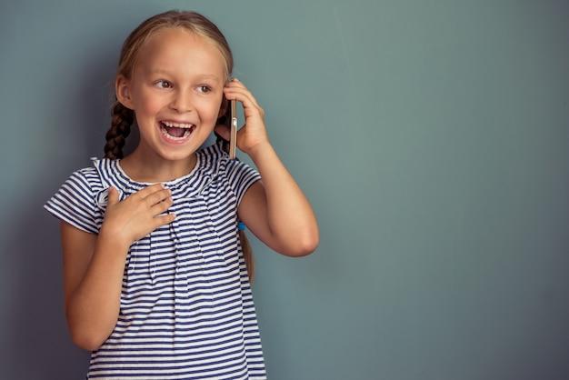 Schattig klein meisje in jurk praat op de mobiele telefoon