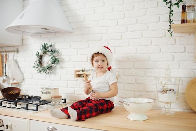 Schattig klein meisje in kerstmuts, koekjes in de keuken thuis voorbereiden. zit op de keukentafel en helpt moeder met het bereiden van een feestelijk kerstdiner
