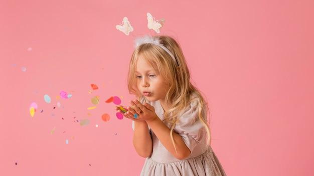 Schattig klein meisje in kostuum waait confetti