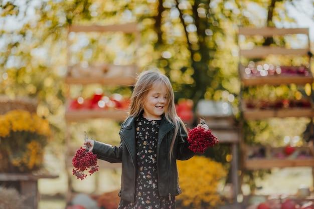 Schattig klein meisje in lederen zwarte jas en herfst jurk poseren met rode as bes