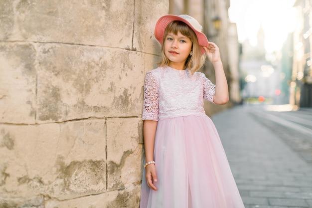 Schattig klein meisje in modieuze roze hoed en jurk poseren voor de camera buiten in de stad straat, permanent in de buurt van oude stenen muur van oud gebouw in europese stad