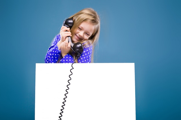 Schattig klein meisje in paarse jurk houdt lege lege plakkaat en telefoonhoorn