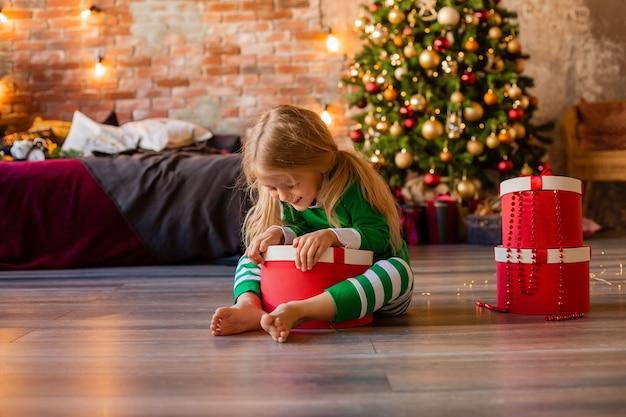 Schattig klein meisje in pyjama's in de buurt van de kerstboom trekt uit de geschenkdoos kitten