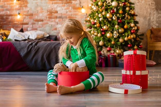 Schattig klein meisje in pyjama's in de buurt van de kerstboom
