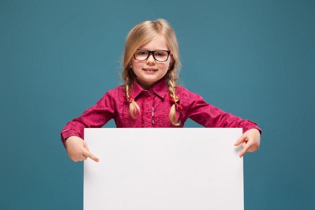 Schattig klein meisje in roze shirt, zwarte broek en bril houdt lege poster