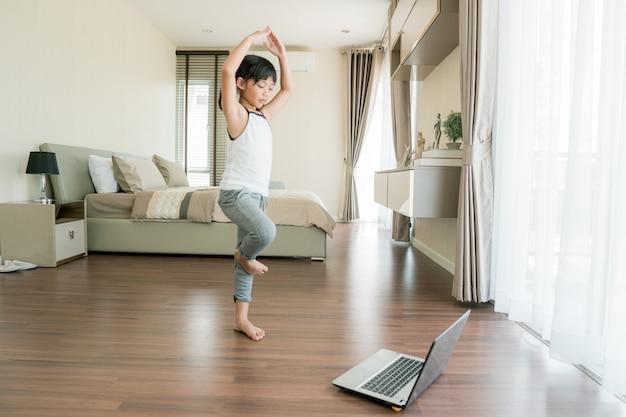Schattig klein meisje in sportkleding die online video op laptop bekijkt en thuis fitnessoefeningen doet.