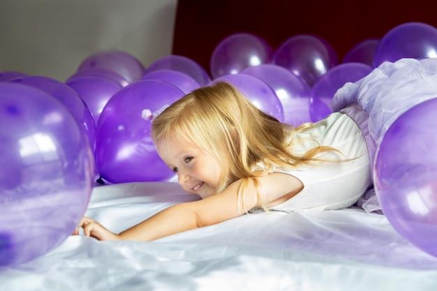 Schattig klein meisje in stijlvolle jurk viert verjaardag met paarse ballonnen
