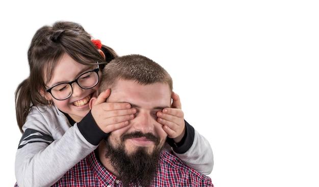 Schattig klein meisje in vrijetijdskleding die de ogen van haar vader bedekt. beide lachend. geïsoleerd op wit. met kopie ruimte