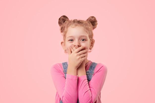Schattig klein meisje in vrijetijdskleding die mond bedekt met handen terwijl het geheim wordt gehouden en camera met glimlach tegen roze achtergrond bekijkt