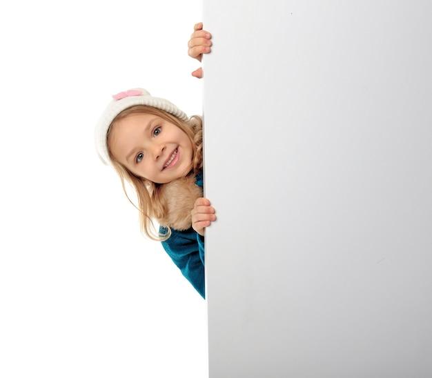 Schattig klein meisje in warme kleren met bord
