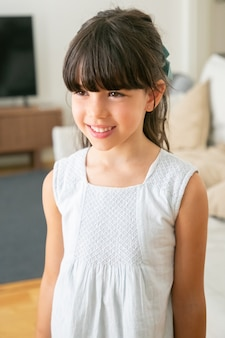 Schattig klein meisje in witte jurk permanent en lachend in de woonkamer.