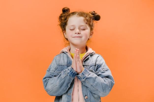 Schattig klein meisje jongen bidden met ogen gesloten op oranje achtergrond Premium Foto
