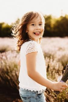 Schattig klein meisje kijken camera glimlachen tonen tong tegen zonsondergang in een veld van lavendel.