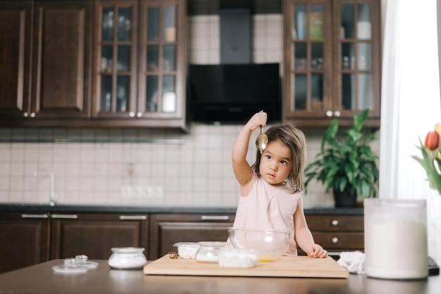 Schattig klein meisje kijkt naar de opgeheven lepel waarmee ze de eieren klopte voor het deeg