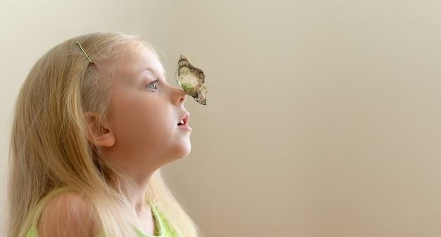 Schattig klein meisje kijkt verbaasd naar een vlinder met vleugels van een biljet van 1000 dollar
