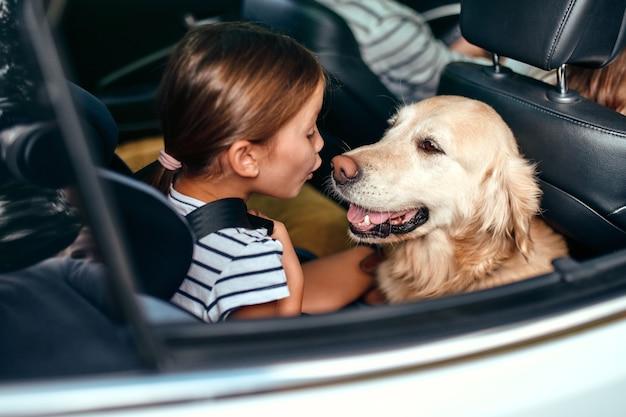 Schattig klein meisje kind in een autostoeltje beschermd door veiligheidsgordels samen met haar vriend hond labrador gaan op weekend. vrije tijd, reizen, toerisme.