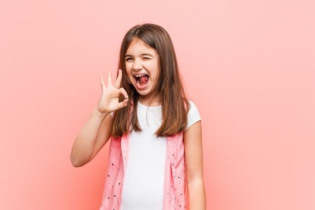 Schattig klein meisje knipoogt en houdt een goed gebaar met de hand.