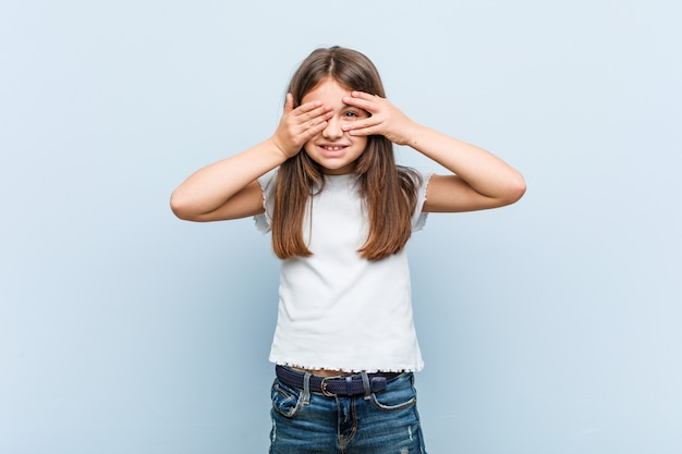 Schattig klein meisje knipperend door vingers bang en nerveus