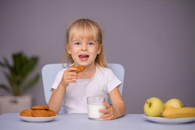 Schattig klein meisje koekjes eten en consumptiemelk thuis of in de kleuterschool