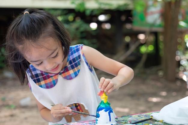 Schattig klein meisje leert gelukkig buiten de klas met prachtige natuur en een stralende glimlach