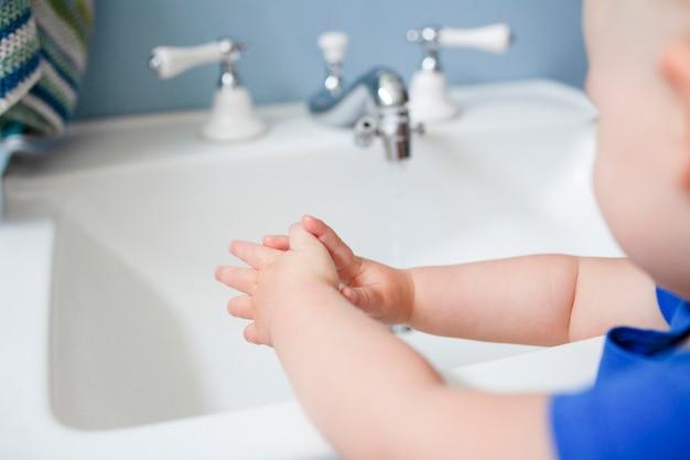 Schattig klein meisje leert hoe ze haar handen moet wassen in het nieuwe normaal