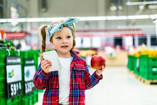 Schattig klein meisje lijst van goederen maken om te kopen in de supermarkt