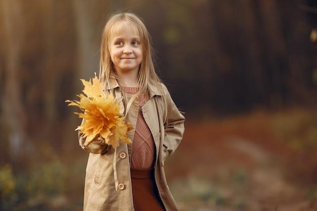 Schattig klein meisje loopt in een herfst park