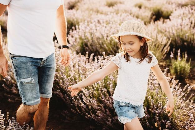 Schattig klein meisje loopt spelen met haar vader in een veld met bloemen.