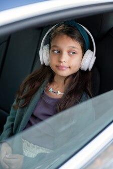Schattig klein meisje luistert naar muziek in een koptelefoon terwijl ze in de auto zit
