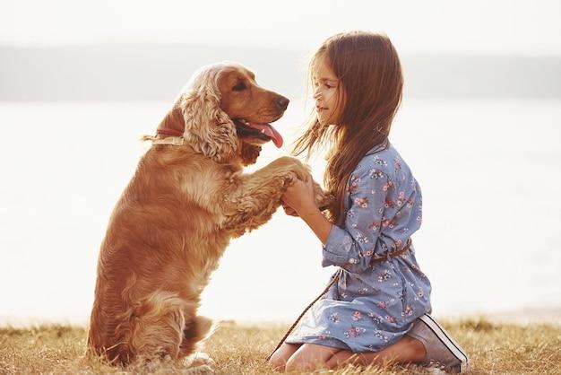 Schattig klein meisje maakt een wandeling met haar hond buiten op een zonnige dag