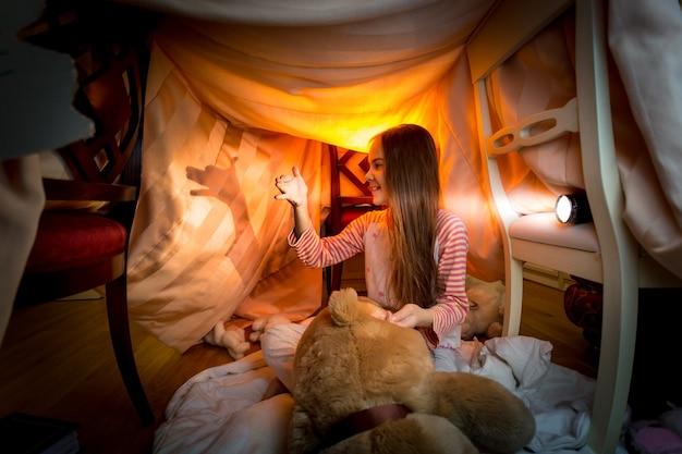 Schattig klein meisje maakt 's nachts theater van schaduwen in de slaapkamer bedroom