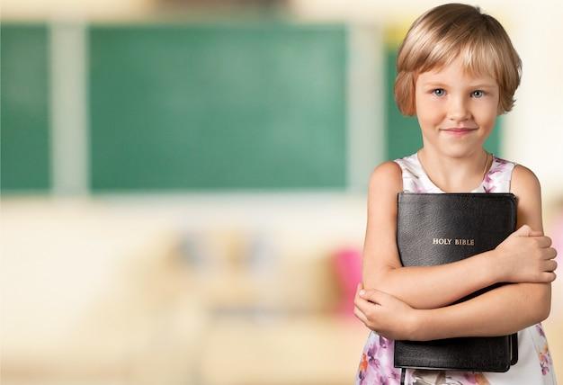 Schattig klein meisje met bijbel op achtergrond