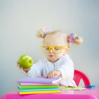 Schattig klein meisje met boeken en groene appel