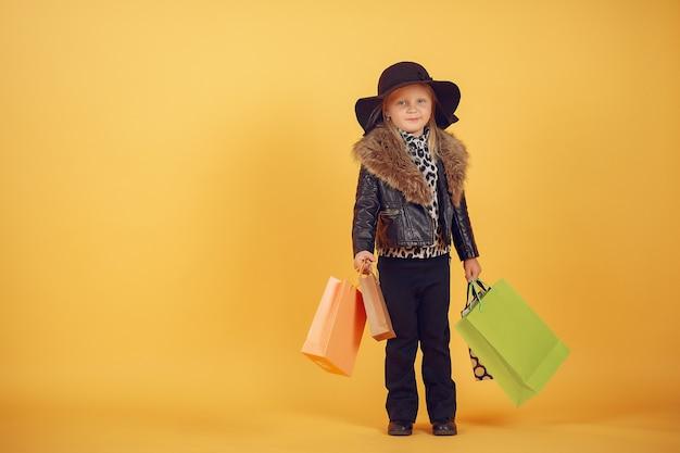 Schattig klein meisje met boodschappentassen op een gele achtergrond