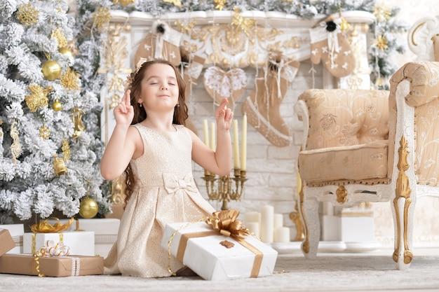 Schattig klein meisje met cadeau zittend in kamer versierd met kerstvakantie