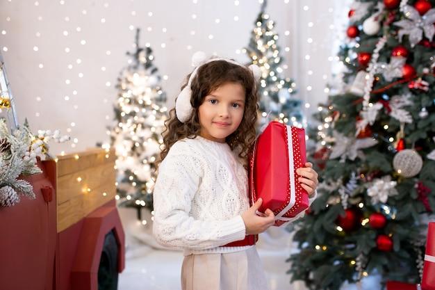 Schattig klein meisje met de doos van de gift van kerstmis in de buurt van kerstbomen met verlichting.
