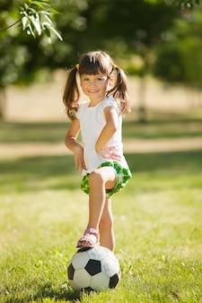 Schattig klein meisje met een bal in een prachtig park
